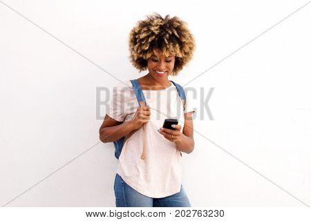 Black Female Student Standing Against White Background And Using Mobile Phone
