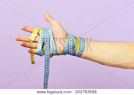Mans hand wrapped with blue and yellow measuring tapes isolated on light purple background close up. Fitness regime and diet concept. Weight management idea. Wrist tied with bicolor flexible rulers