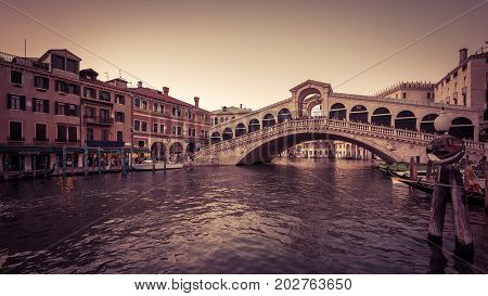 Rialto Bridge over the Grand Canal in the evening in Venice, Italy. Rialto Bridge (Ponte di Rialto) is one of the main tourist attractions of Venice. 16:9 widescreen.