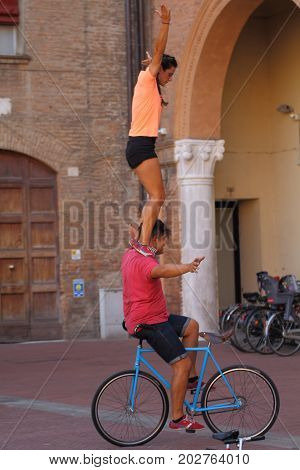 Ferrara, Italia - August 27, 2017: The Ferrara Buskers Festival is dedicated to the art of the street. Artists perform in flying acrobats on the bicycle. Buskers Festival. Cia. Alta Gama