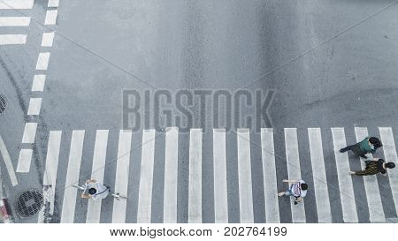 Crowd of people walk on street pedestrian crossroad in the city street from top view bird eye view.