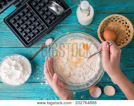 Making waffles at home - waffle iron, batter in bowl and ingredients - milk, eggs and flour. Cooking background.