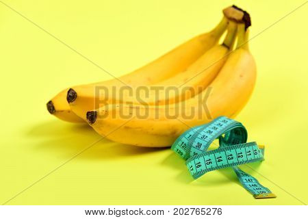 Tape For Measuring In Turquoise Color Next To Bunch Of Bananas