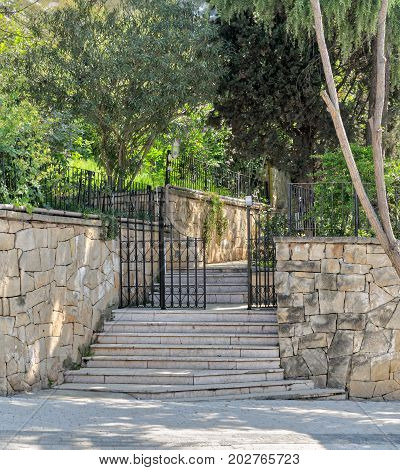 Ascending marble stairs leading to a public park Stone wall and fence iron door Buyukada Island Istanbul Turkey