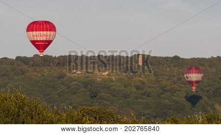 BATH UK - 28 AUG 2017 Liveried hot air balloons in front of Brown's Folly. Red and white balloons carrying people above countryside in Somerset England