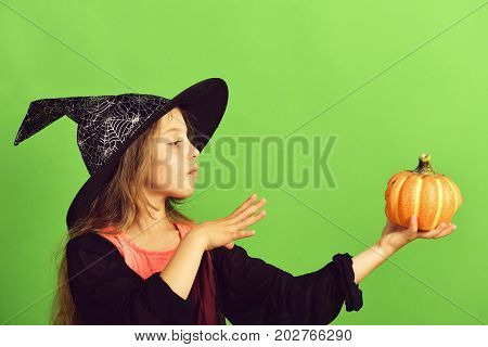Kid In Black Witch Hat, Dress And Concentrated Face