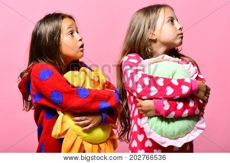 Friends in pink pajamas isolated on pink background. Girls with loose hair hug pillows and look aside. Kids with surprised faces hold green and yellow pillows. Pajama party and childhood concept