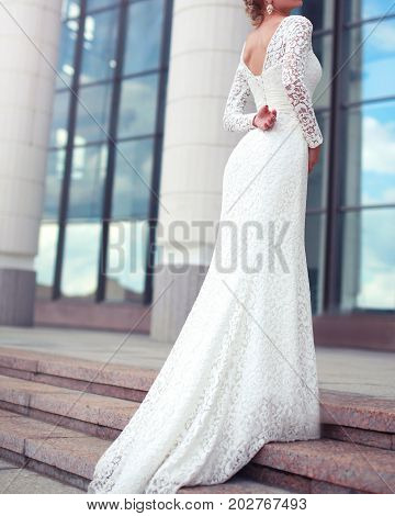 Elegant Woman Bride In White Wedding Lace Dress Posing In The City