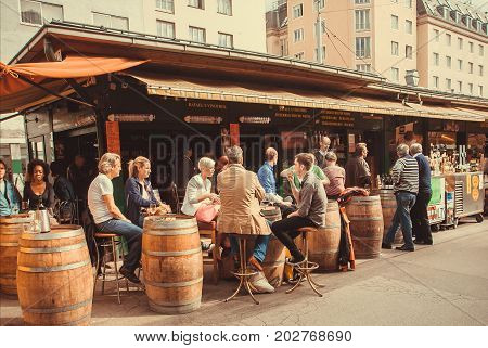 VIENNA, AUSTRIA - JUN 6, 2013: Barrels like tables and people around in cafe or bar in outdoor area of Naschmarkt popular market of the city on June 6, 2013. Food and drinks market works from 1793