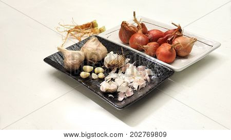 Red onion and garlic with blur coriander root are herbs for cooking Macro photo focus select at center of picture.