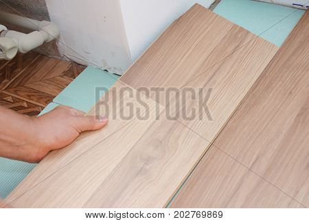 Contractor install wooden laminate flooring with insulation and soundproofing sheets in problem area.