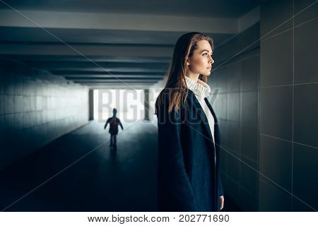 Beautiful Lonely Woman In Subway Tunnel With Frighten Silhouette On Background