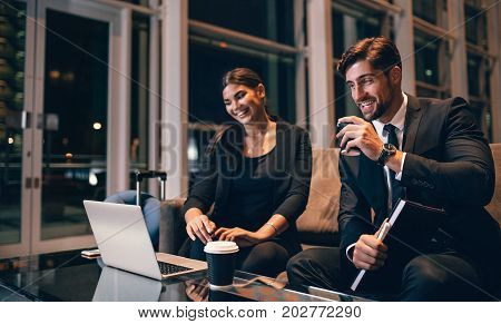 Young businessman and woman waiting at airport lounge and looking at laptop. Business travelers waiting for their flight at airport terminal.