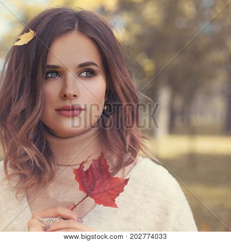 Beautiful Young Woman Fashion Model with Red Fall Mapple Leaf Outdoors Autumn Beauty