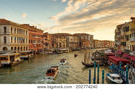 Venice, Italy - May 17, 2017: Water taxis and gondolas are sailing along the Grand Canal at sunset. Grand Canal is one of the major water-traffic corridors in Venice.