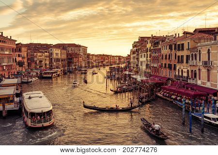 Venice, Italy - May 17, 2017: Gondolas and motor boats are sailing along the Grand Canal at sunset. Grand Canal is one of the major water-traffic corridors in Venice.