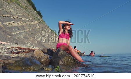Girl teenager sits on sea on a rock. Dreams in the distance of dreams childhood rest sea