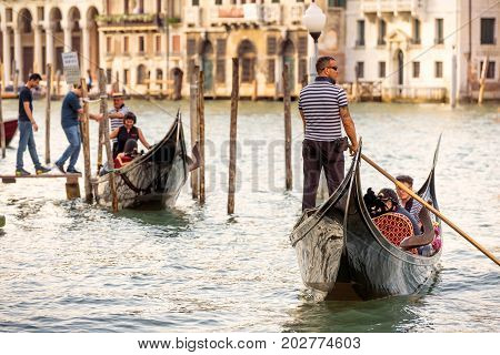 Venice, Italy - May 18, 2017: Gondolas with tourists are sailing along the Grand Canal. Gondola is the most attractive tourist transport in Venice.
