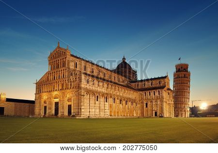 Leaning tower and cathedral at night in Pisa, Italy as the worldwide known landmark.