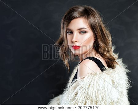 Beauty Fashion Model Girl with Curly Bob Hairstyle. Woman in White Fur Coat. Beautiful Luxury Winter Woman on Black Background