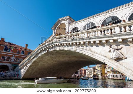 Venice, Italy - May 21, 2017: Rialto Bridge with tourists over the Grand Canal. Rialto Bridge (Ponte di Rialto) is one of the main tourist attractions of Venice.