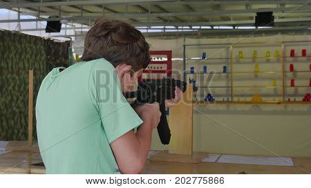 Boy teen shoots in dash from the machine gun. Airguns gun. boy lifestyle gun