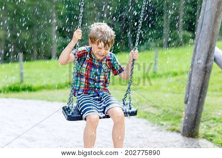 Funny kid boy having fun with chain swing on outdoor playground during rain. child swinging on warm rainy summer day. Active leisure with kids. Happy boy with rain drops on face