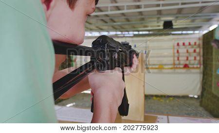 Boy teen shoots in dash from the machine gun. Airguns