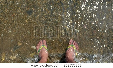 man legs stand in sea water waves. Sea the ocean holidays