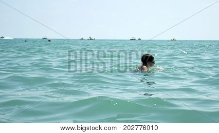 Beautiful boy and sea. Boy teen swims in the ocean sea. Summer vacation on the water