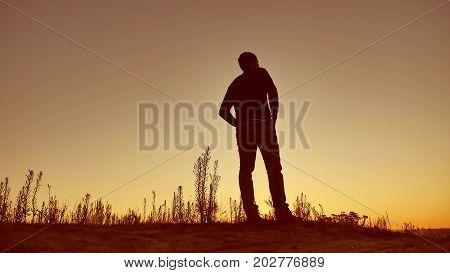 man silhouette. Man walking on summer sunset meadow. man sunset travel slow motion video
