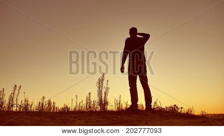 Man travel silhouette. Man shows his hand in distance standing on mountain silhouette sunlight sunrise