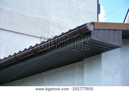 Close up on house plastic roof gutter with soffit and fascia board.