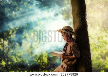 Boy scout is reading book at under tree