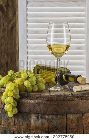 Still life of white wine with wooden keg vertical. Wine bottle glass of white wine and bunch of grapes on a old wooden barrel. Wine tasting and production concept.