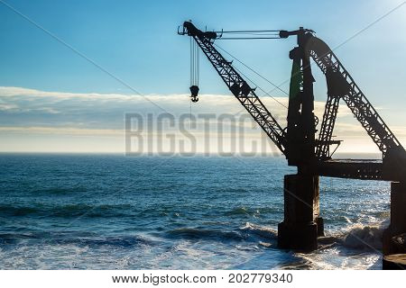 Silhouette of an old abandoned crane in the Pacific Ocean in Vina del Mar Chile