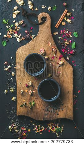 Chinese black tea in black stoneware cups on serving wooden board over black wooden background with herbs, flower buds, tea leaves spilt around, top view