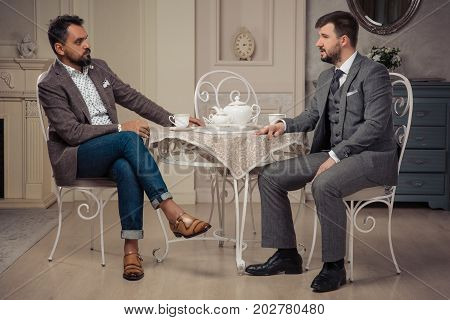 Two imposimg men conduct a small talk at the table in retro studio