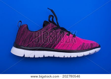 Pink And Black Sport Woman Shoes Isolated On Blue Background.