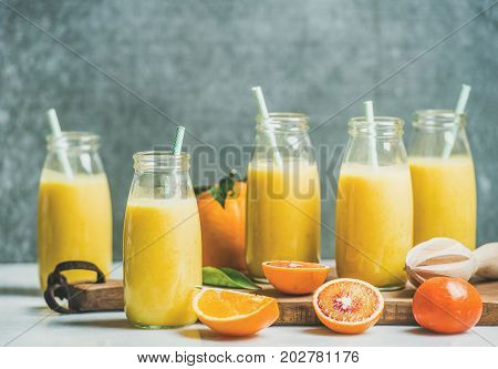 Healthy yellow smoothie with citrus fruit and ginger in bottles on rustic wooden board over light marble table, selective focus, copy space. Clean eating, vegan, dieting, weight loss food concept