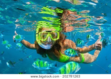 Happy family - girl in snorkeling mask dive with tropical fishes in coral reef sea pool. Travel lifestyle water sports outdoor adventure underwater swimming on summer beach holiday with kids.