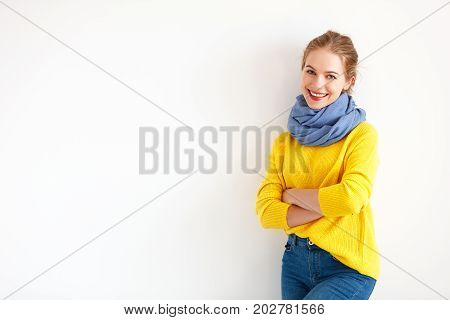 happy young woman in a yellow sweater on a white background