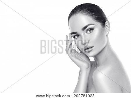 Beautiful Spa Brunette Woman Touching her Face. Perfect Fresh Skin. Beauty Portrait. Pure Beauty Model Girl. Youth and Skin Care Concept. Black and white portrait