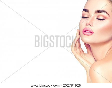 Beautiful Spa Brunette Woman Touching her Face. Perfect Fresh soft Skin. Blissful Beauty Portrait. Pure Beauty Model Girl. Youth and Skin Care Concept. Isolated on white background