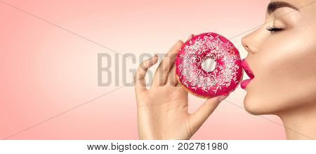 Beautiful Woman eating pink donut. Beauty fashion model girl enjoying food, eating colorful  doughnut. Fashion make-up, pink lipstick. Diet, dieting concept. Junk food, weight loss