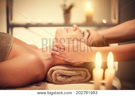 Spa woman Massage. Face Massage in beauty spa salon. Female enjoying relaxing body and facial massage in spa center. Body care, skin care, wellness, beauty treatment