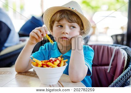 Cute healthy preschool kid boy eats french fries potatoes with ketchup sitting in cafe outdoors. Happy child eating unhealthy food in restaurant.