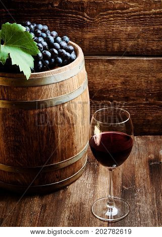 Glass of wine on wooden table with ripe grapes of wine and wooden barrel.