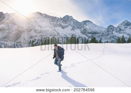 Representative image of the winter season with snowy mountain peaks fir forest and a man wandering through a thick layer of snow in Ehrwald Austria.