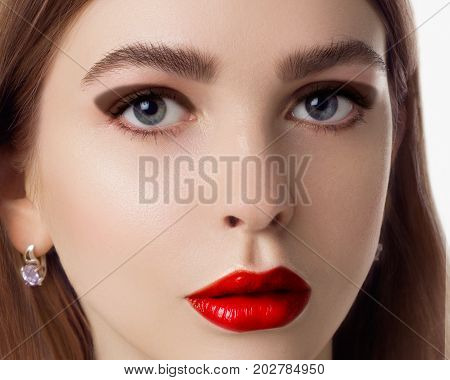 The beautiful femme fatale with a bright make-up and a captivating look. Fashionable make-up close up. Fashion photo